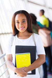 college student holding black & yellow books
